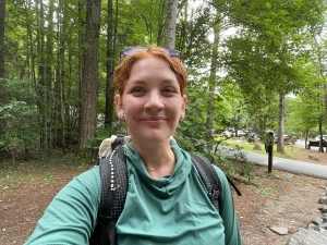 A selfie of a woman softly smiling, wearing a backpack on a dirt trail.